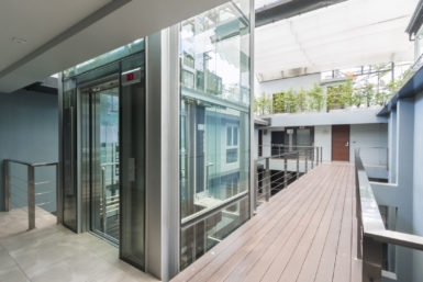 apartment interior with walkway bridge and glass lift opened.