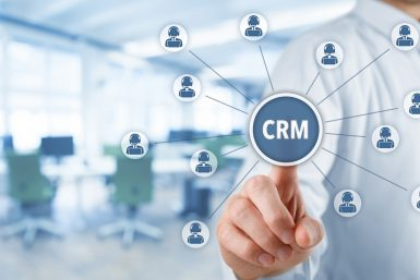 "Customer relationship management (CRM) concept. Businessman click on virtual scheme representing CRM (or customer service). Wide banner composition with office in background.""n"